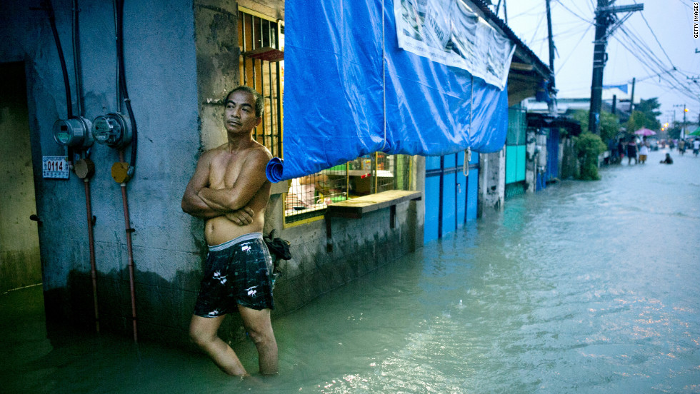 A man stands in a flooded street in Bulacan on Tuesday, August 14, as more rain falls on the region.