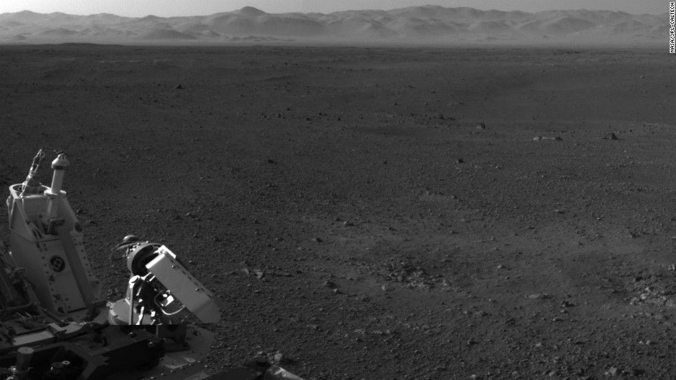 "This image, with a portion of the rover in the corner, shows the wall of ""Gale Crater"" running across the horizon at the top of the image."