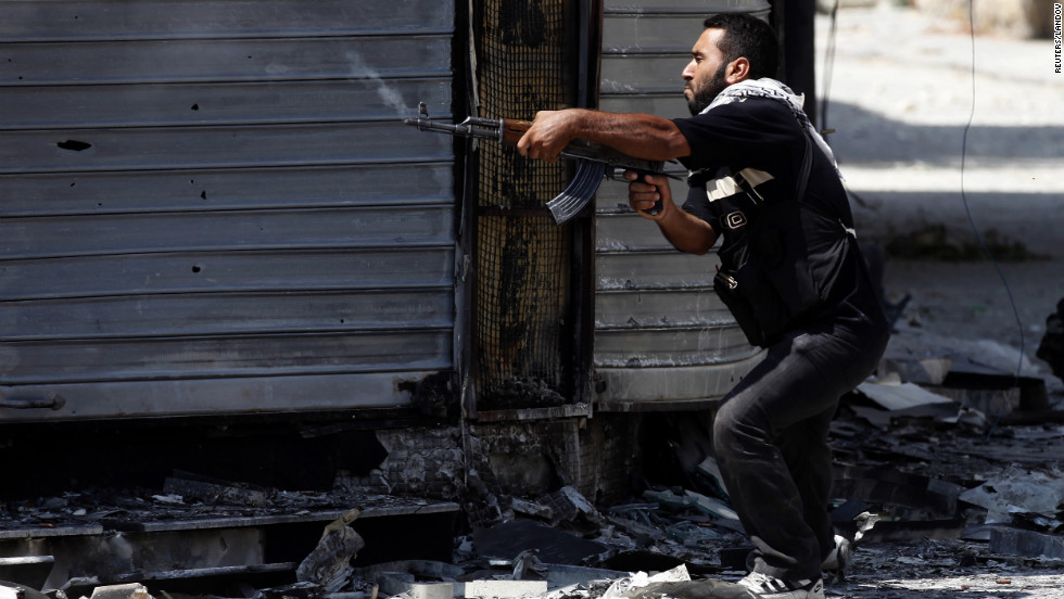 A Free Syrian Army fighter fires an AK-47 rifle in Aleppo on Wednesday, August 15.