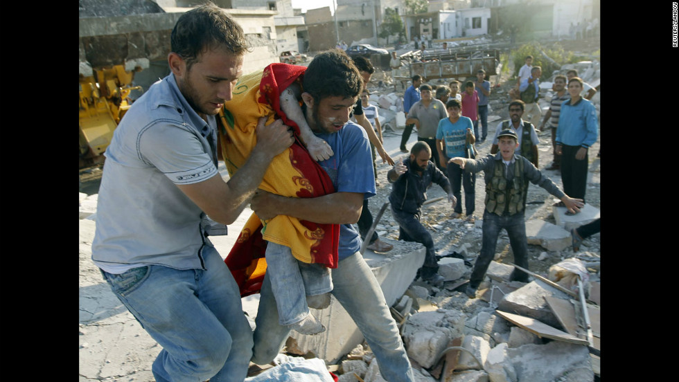 A man carries the body of a boy after a Syrian Air Force strike on Azaz, some 29 miles north of Aleppo.