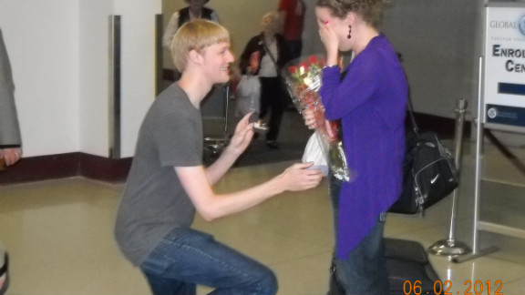 """Melissa Sneed arrived at the Charlotte airport thinking her partner, Chris, was in New York. To her surprise, Chris was waiting at baggage claim, surrounded by family. """"We have been dating long distance for much of our relationship, so being proposed to in the airport, meant a lot to both of us."""" Check out the video of Chris"""