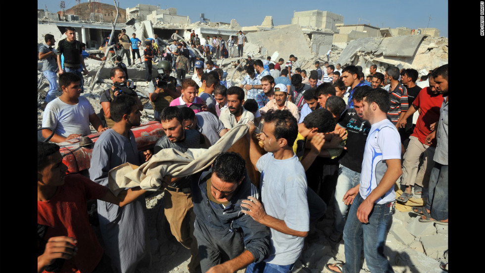 Syrians carry the body of a woman after an airstrike in Azaaz.