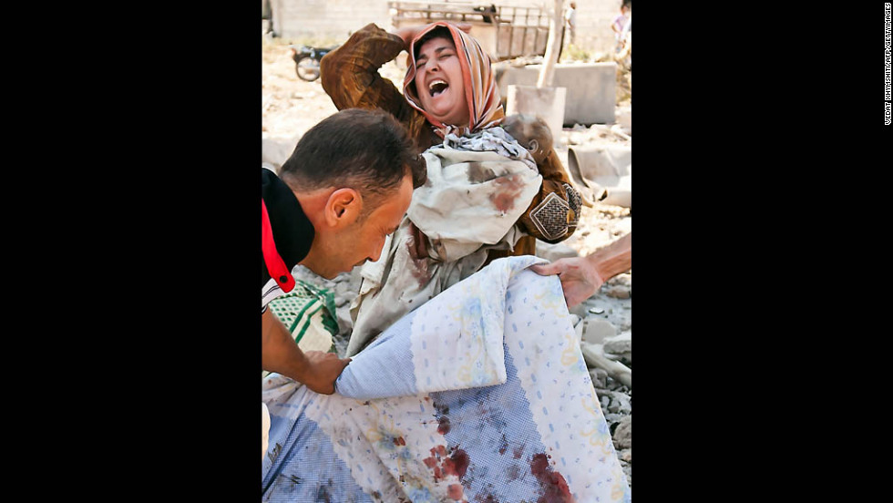 A grief-stricken woman clutches her dead baby while her husband's body is covered up following a regime airstrike on Azaz, a town near Aleppo, on Wednesday, August 15.