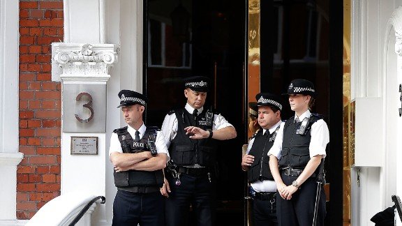Police stand guard outside the Ecuadorian Embassy in London.