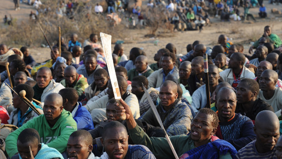 Striking workers are monitered by police during a sit-in on a hill as they demad a wage increase.