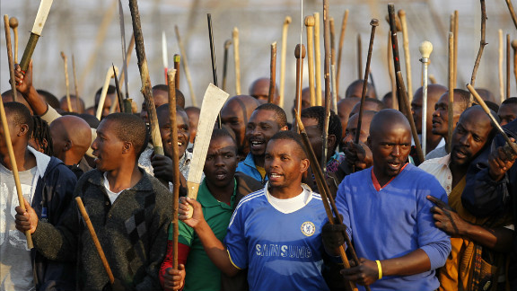 Armed workers chant slogans outside the mine.