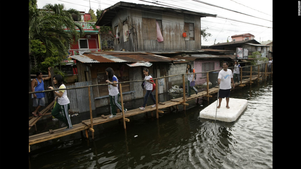 Filipino students walk on a footbridge on a road that remains flooded a week after heavy monsoon rains in Taguig City, south of Manila, Philippines, August 16, 2012. A tropical storm hit the Northern Luzon, bringing days of wet weather to a region still recovering from massive flooding. According to the Office of Civil Defense, the floods have left at least 96 people dead and affected up to 2.68 million people.