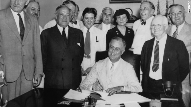 President Roosevelt signs the 1935 Social Security Act into law. Lawmakers now discuss cutting defense and entitlement spending.
