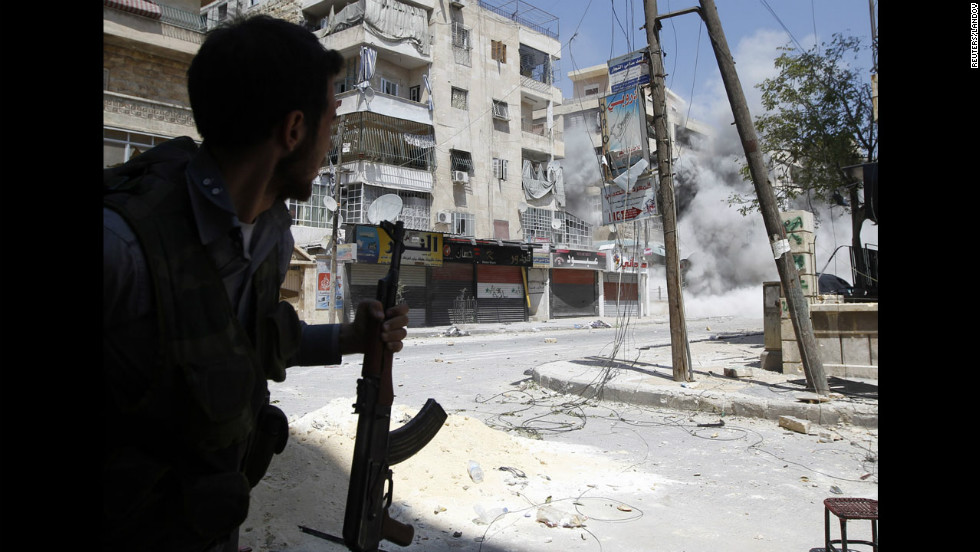 A rebel fighter runs for cover as a Syrian army tank shell hits a nearby building Friday in Aleppo. The opposition accuses Syrian forces of shelling flashpoint neighborhoods in Aleppo where rebels are making a stand.