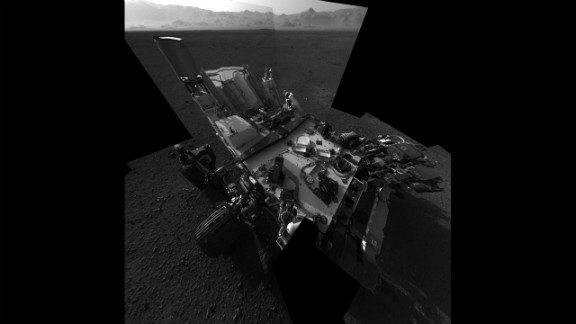 "An updated self-portrait of the Mars rover Curiosity, showing more of the rover's deck. This image is a mosiac compiled from images taken from the navigation camera. The wall of ""Gale Crater,"" the rover's landing site, can be seen at the top of the image."