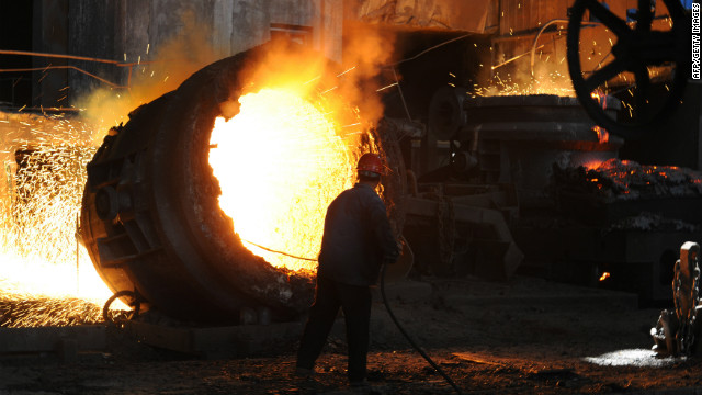 This photo taken on June 25, 2011 shows a worker stoking a giant burning cauldron at a steel mill in Hefei, China.