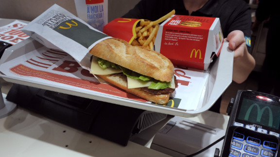 An employee displays the McBaguette, a burger-filled sandwich tested earlier this year at McDonald's restaurants in France.