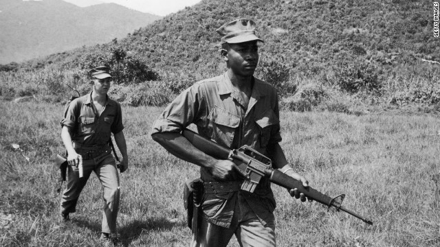 Soldiers Lance Corporal Murphy (R) and Sergeant Paige patrol a jungle area, carrying a rifle and a pistol during the Vietnam War, 1960s. (Photo by Express Newspapers/Getty Images)