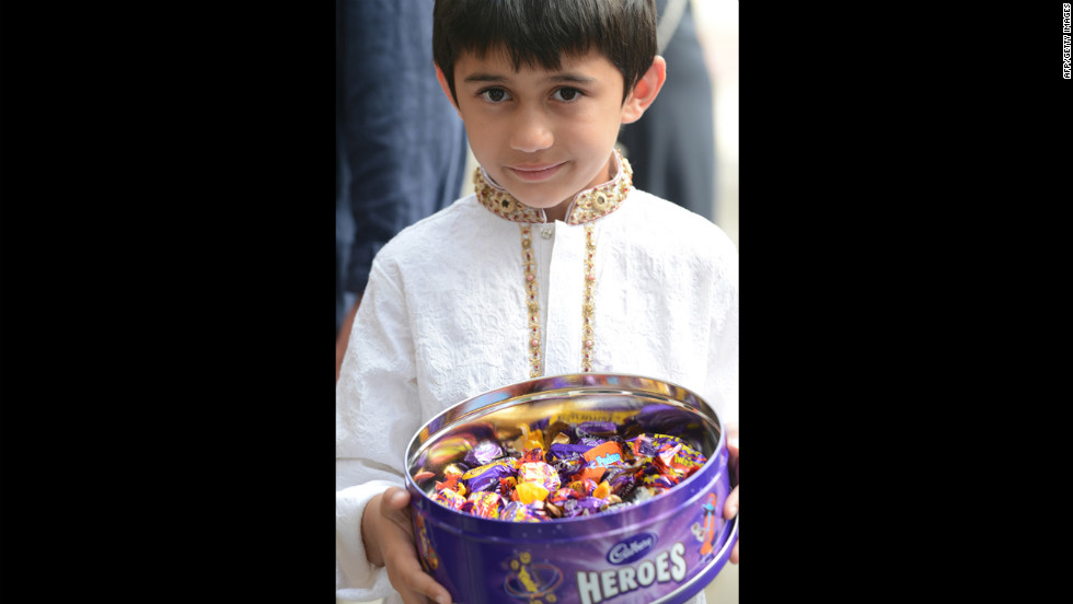 A young boy holds a tin of candy to distribute at the Regent's Park Mosque in London, England, after prayers on Eid al-Fitr on Sunday.