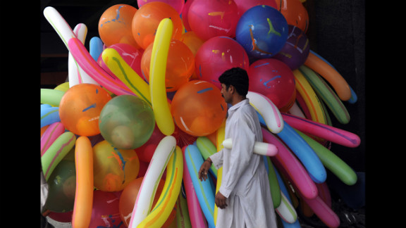 A Pakistani balloon vendor waits for customers near a mosque where Muslims offer Eid al-Fitr prayers in Karachi on Monday.