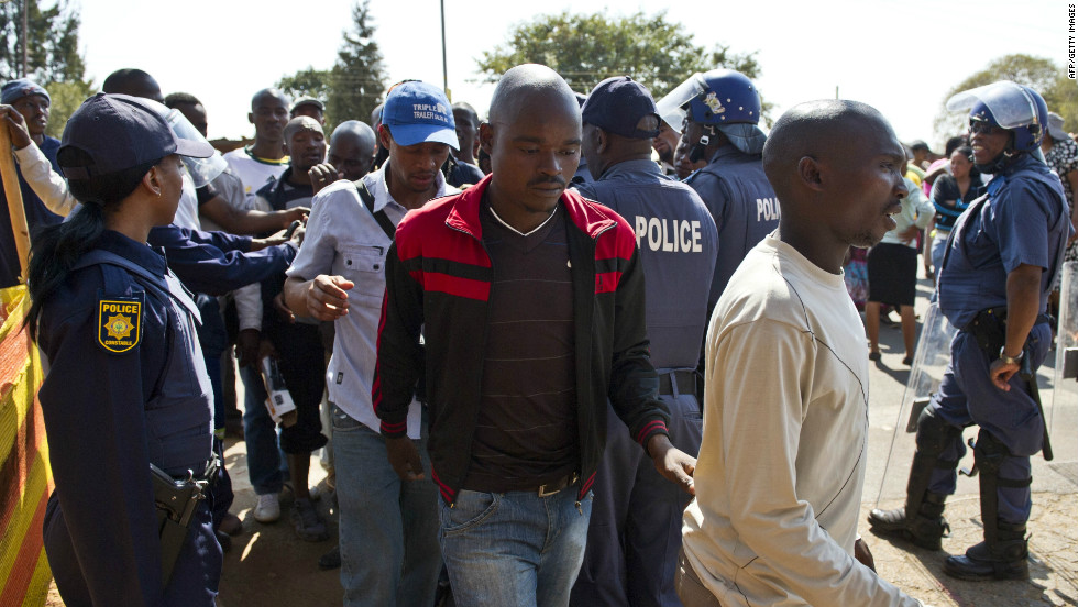 Miners arrested for allegedly being involved in violent clashes between striking workers and police are escorted from the Ga-Rankuwa courthouse, Pretoria, on August 20.