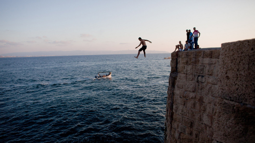 An Israeli Arab leaps into the sea from the walls of the old city of Acre on Monday.