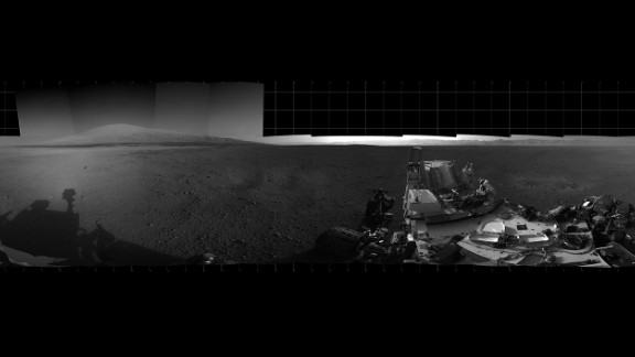"With the addition of four high-resolution Navigation Camera, or Navcam, images, taken on August 18, 2012. Curiosity's 360-degree landing-site panorama now includes the highest point on ""Mount Sharp"" visible from the rover. Mount Sharp's peak is obscured from the rover's landing site by this highest visible point."