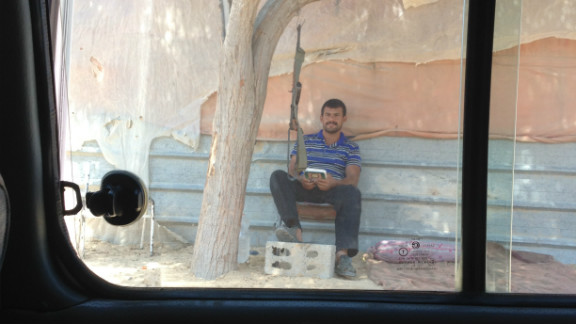 A Hamas security guard reads the Quran at the entrance to one of the smuggling tunnels.
