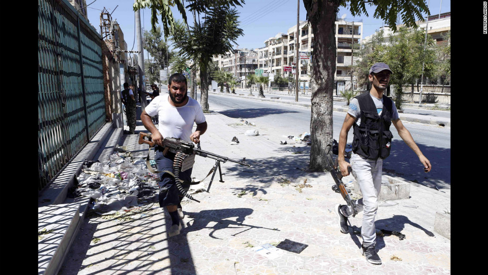 Syrian rebels run for cover during heavy fighting in the Saif al-Dawla district in the center of Aleppo on August 22.