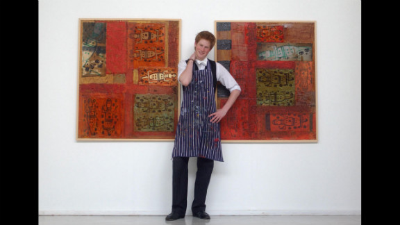 In 2003, Harry stands between some artwork he completed while studying at Eton College.