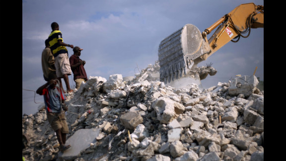 A group of men gather iron while rubble of a earthquake destoryed building t is removed. in Port au Prince, on January 8, 2011.