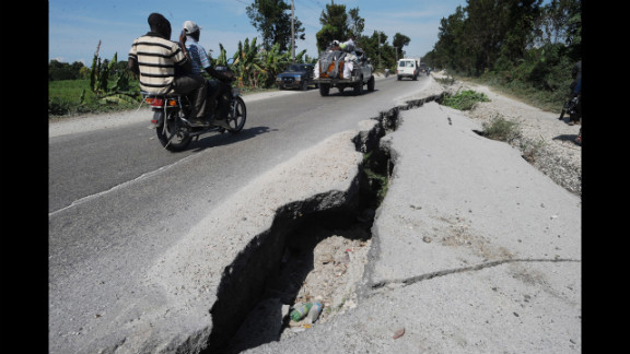 Haitians drive down a still-damaged road in Leogane a year after the devastating earthquake.