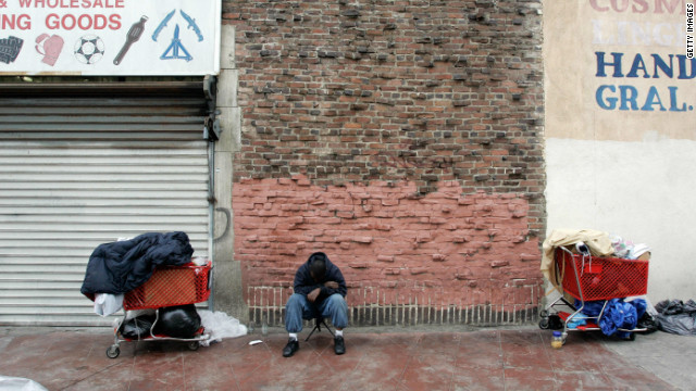 A homeless man sits with his belongings near downtown Los Angeles.