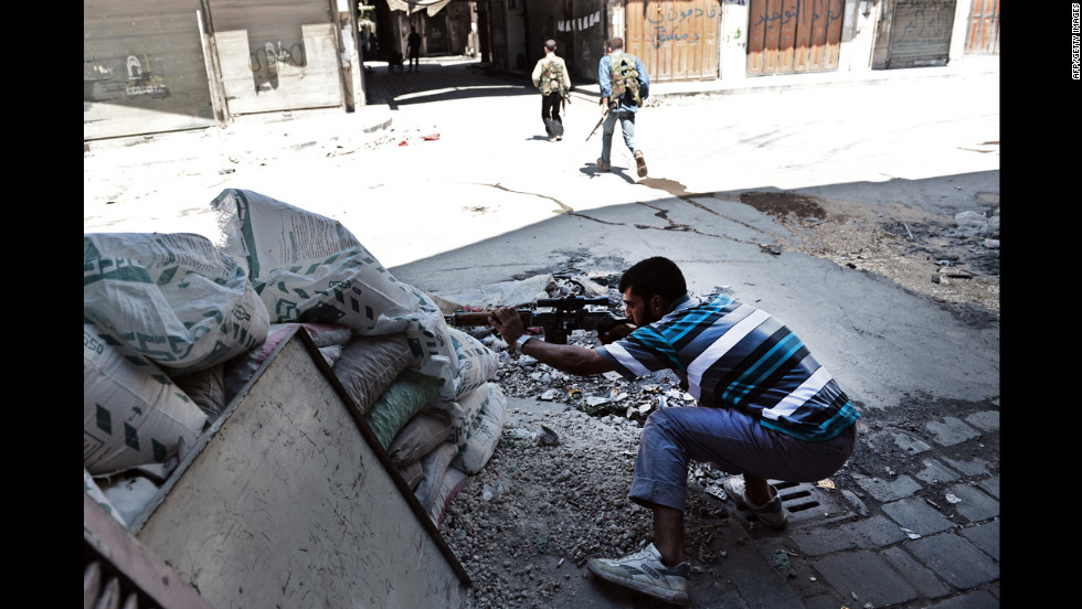 A Free Syrian Army fighter takes aim at regime forces during clashes in Aleppo.
