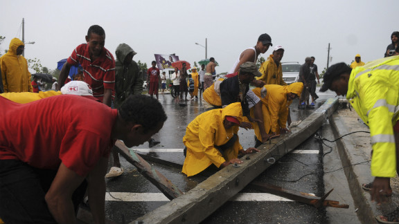 Workers remove an electrical post blown down by Tropical Storm Isaac in Jaquimeyes, Barahona province.