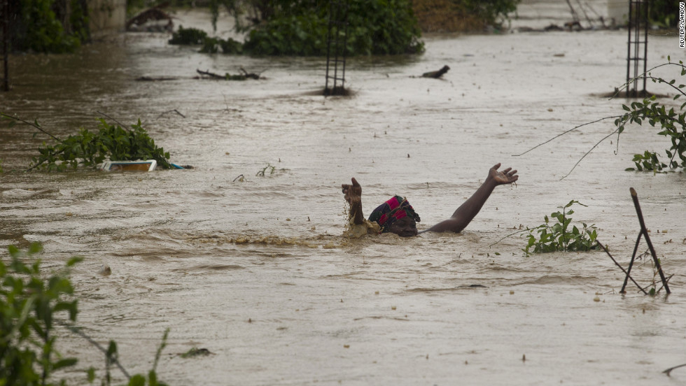 A woman wades through flood waters to try to save her possessions from her flooded home in Port-au-Prince.