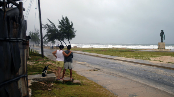 A couple watch as waves and strong winds from Tropical Storm Isaac, which crossed Cuba on Sunday, batter the shore in Gibara, Cuba, on Saturday.