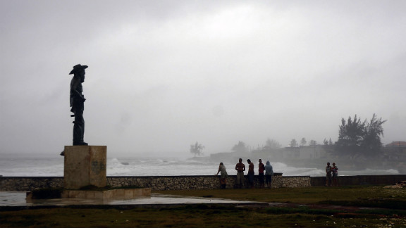 People watch from the shore as waves pound the coast in Gibara.