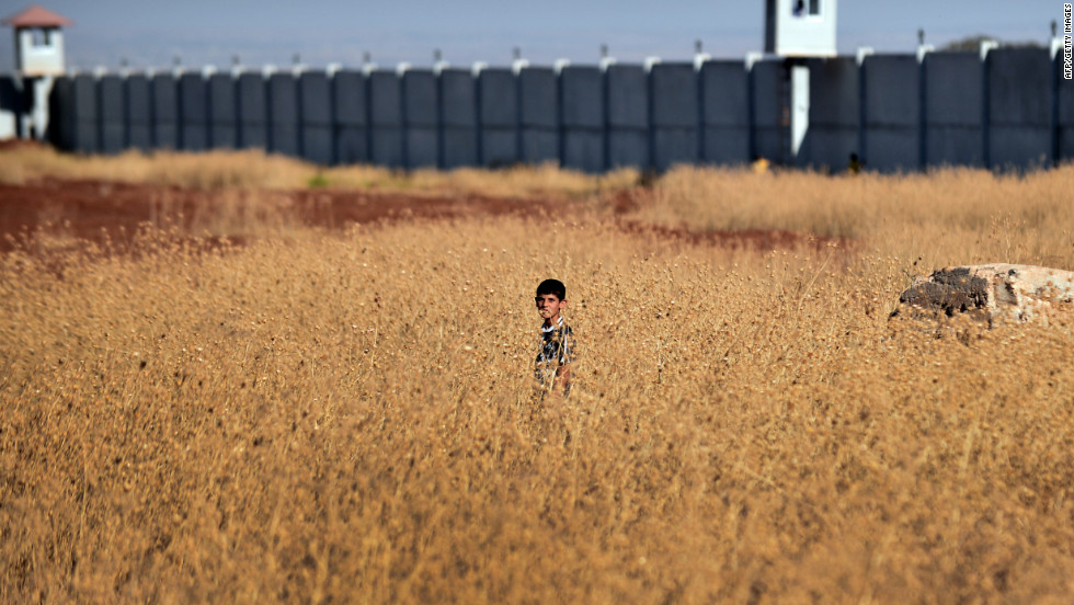 A Syrian boy whose family has been displaced due to fighting between rebel fighters and Syrian government forces stands in a field near the border with Turkey.