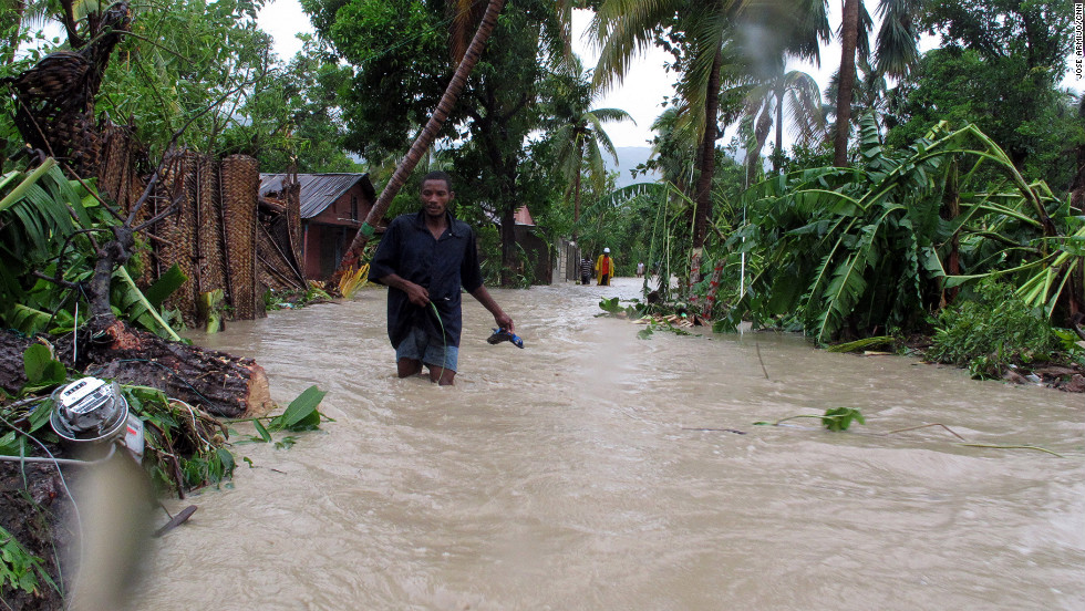 "Residents of Jacmel, Haiti, make their way through floodwaters as Tropical Storm Isaac dumps heavy rains in August 2012. An extreme exposure to climate-related events, combined with poor health care access, weak infrastructure, high levels of poverty and an over-reliance on agriculture have led to the country being categorized as at ""extreme"" risk."