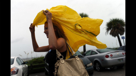 Rachel Bolch Thach tries to shelter herself from the rain in Tampa. Tropical Storm Isaac is expected to bring rain and wind to the area and has caused convention officials to delay the start of the convention until Tuesday.