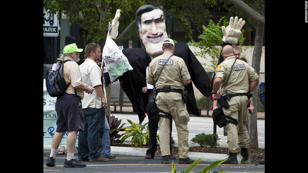 Police officers question protesters carrying an effigy of Republican Party presidential candidate Mitt Romney during a demonstration in downtown Tampa.
