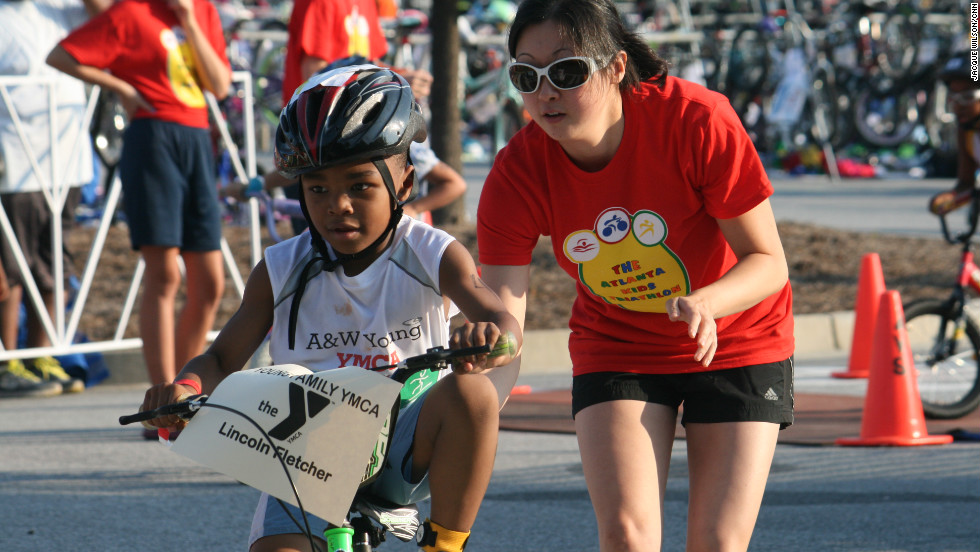 A volunteer gives Lincoln Fletcher a push to send him on his three-mile bike ride.