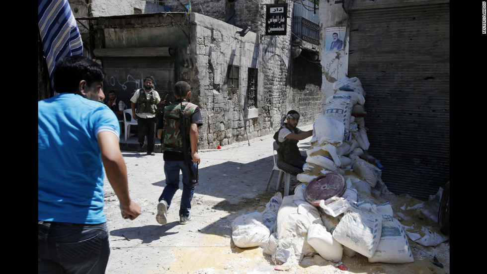 Free Syrian Army fighters run for cover in the old city of Aleppo on Monday.