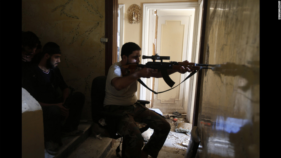 A Free Syrian Army sniper takes his position in Seif El Dawla on Monday.