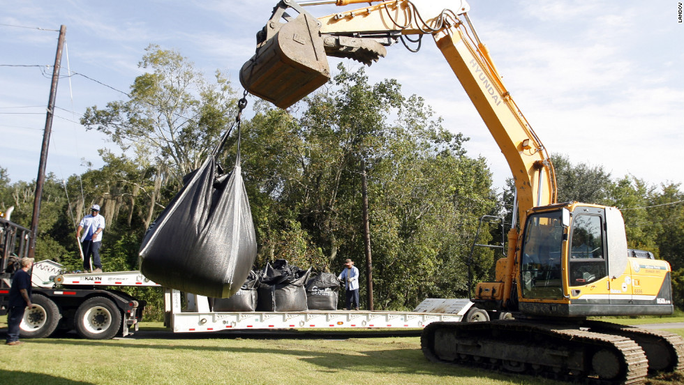 A crew from Jefferson Parish Drainage Department places large sandbags near  a canal and pond in