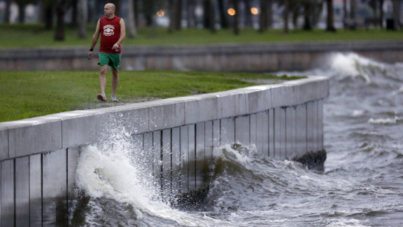 A St. Petersburg, Florida, resident walks along the sea wall at Spa Beach, where larger than average waves were being kicked up by Tropical Storm Isaac on Monday.