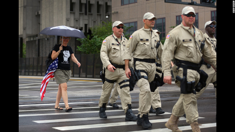 Lynne David walks behind a group of law enforcement officers as they patrol the streets before the convention.
