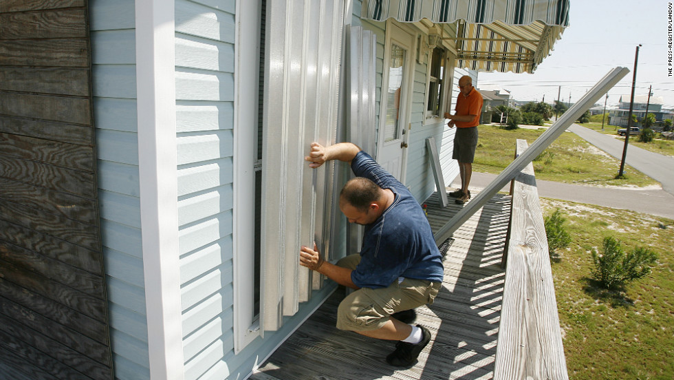 Larry Hoffmeister, left, and Charles Carter place storm shutters on Carter's vacation home on Dauphin Island, Alabama, as they prepare for  Isaac on Sunday.