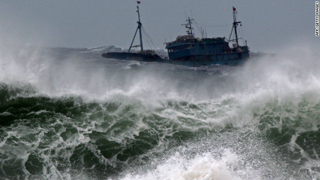 A Chinese fishing boat fights high waves after taking shelter in a port on Jeju on August 27, 2012, ahead Typhoon Bolaven.