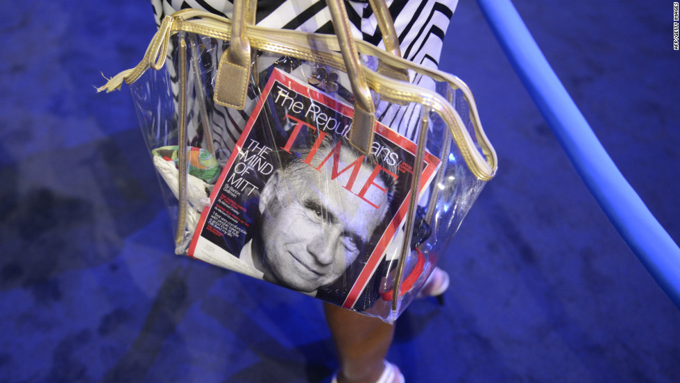A convention attendee carries a bag with a Time magazine featuring Mitt Romney on the cover.