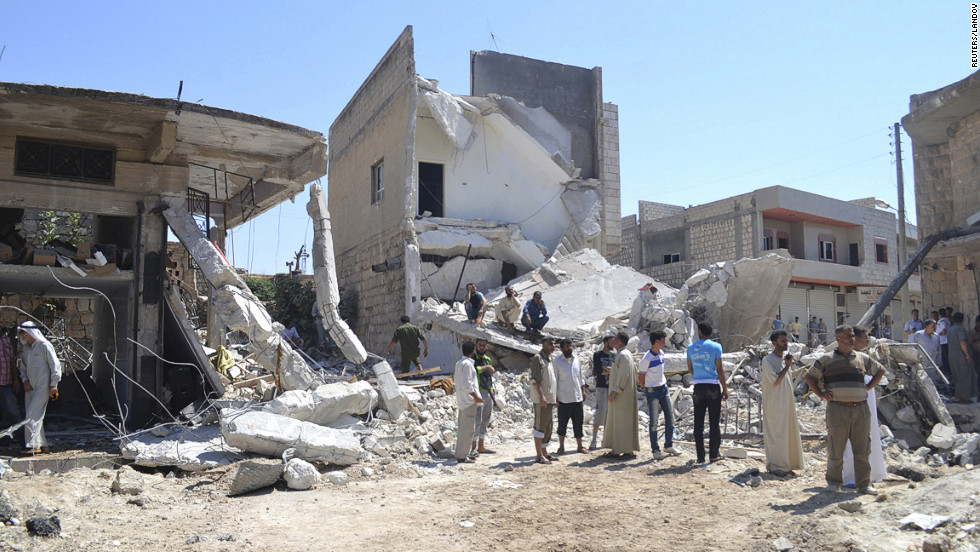 Residents walk past buildings damaged in what activists said was an airstrike by the Syrian air force on Kafranbel, near Idlib.