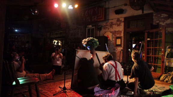 """Members of The Autonomous Playhouse, a troupe of puppeteers, perform """"Momma Nature vs. the Foreclosure Crisis,"""" a puppet show about capitalism, foreclosures and the right to own a home, at New World Brewery."""