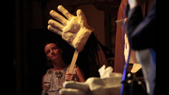 """Kathy Morris plays the role of """"Ann Momney"""" as she controls the hands of """"Ritt Momney"""" while the puppet engages in a mock political debate with Vermin Supreme, not pictured, at New World Brewery."""