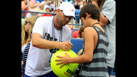 Golfer Sergio Garcia of Spain signs an autograph for a fan as James Blake of the United States and Lukas Lacko of Slovakia compete.